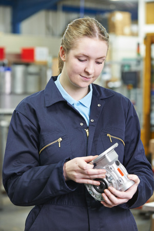 component: Female Apprentice Engineer Checking Component Stock Photo