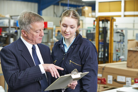 19 year old: Factory Manager And Apprentice Engineer Looking At Clipboard