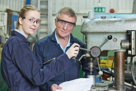 19 year old: Engineer Showing Female Apprentice How To Use Drill