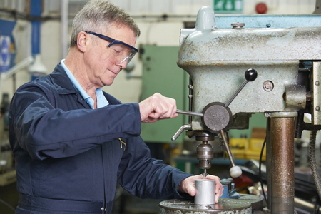 machinist: Skilled Engineer Using Drill In Factory Stock Photo