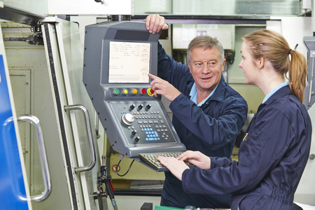 19 year old: Engineer Showing Apprentice How to Use Computerized Cutting Mach