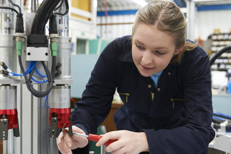 19 year old: Female Apprentice Engineer Working On Machine In Factory