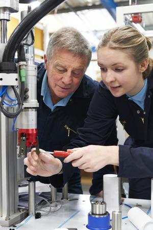 maquinaria: Ingeniero Y Mujer aprendiz que trabajan en maquinaria En F�brica Foto de archivo