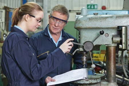 machinist: Engineer Showing Apprentice How to Use Drill In Factory