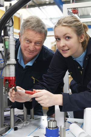 19 year old: Engineer And Female Apprentice Working On Machine In Factory Stock Photo