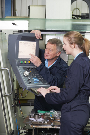 19 year old: Engineer And Apprentice Using Computerized Cutting Machine