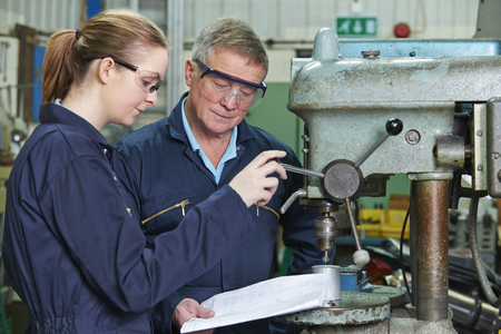 19 year old: Engineer Showing Female Apprentice How To Use Drill In Factory