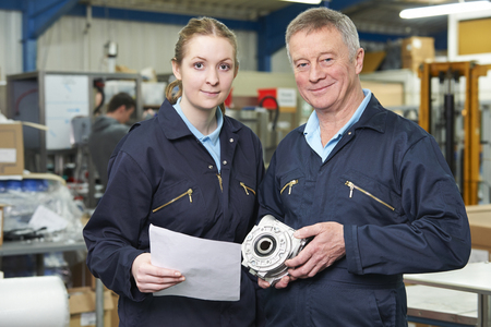19 year old: Engineer With Apprentice Looking at Component In Factory