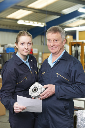 19 year old: Engineer And Apprentice With Component In Factory Stock Photo