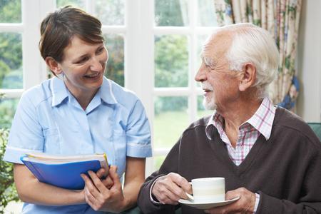 men talking: Senior man With Carer At Home