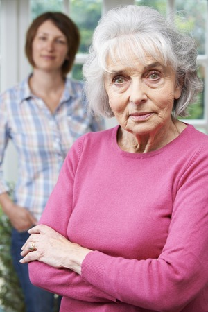 grown ups: Serious Senior Woman With Adult Daughter At Home