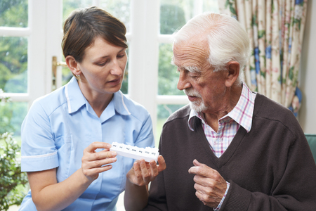 assisted living: Carer Helping Senior Man With Medication Stock Photo