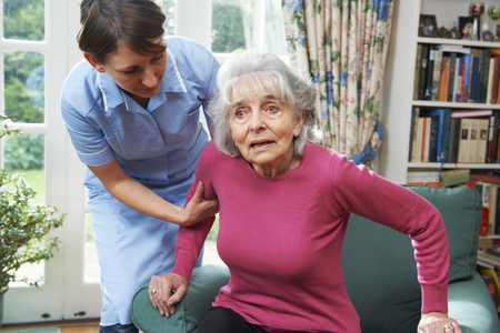 Carer Helping Senior Woman Out Of Chair Stock Photo