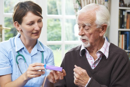 advising: Nurse Advising Senior Man On Medication At Home Stock Photo
