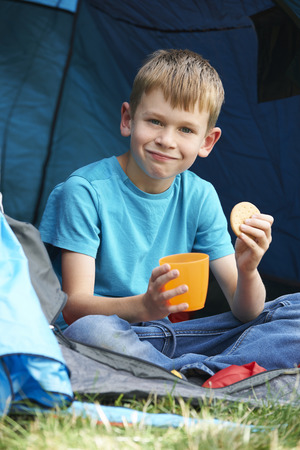 7 year old boys: Boy Having Snack On Camping Trip Stock Photo