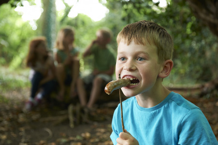 7 year old girl: Boy Eating Sausage Cooked On Campfire With Friends