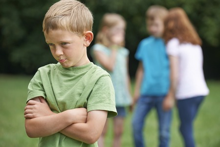 7 year old girl: Unhappy Boy Being Gossiped About By Other Children Stock Photo