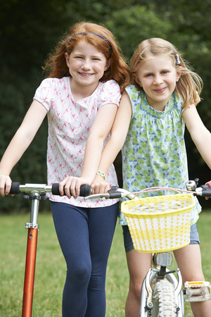 7 year old girl: Two Girls Riding Bike And Scooter Together Stock Photo