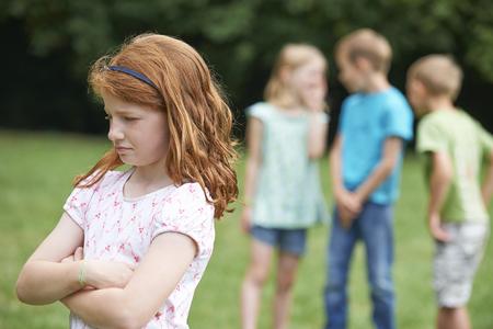 Ongelukkig meisje dat wordt geroddeld over door andere kinderen
