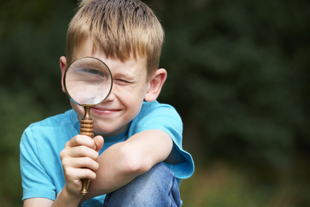 kinder spielen: Boy Blick durchs Vergrößerungsglas mit Vergrößerte Augen