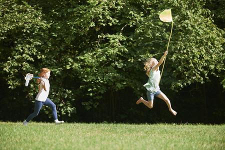 Two Girls Chasing Butterflies In Summer Field