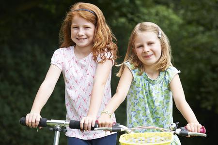 niñas jugando: Dos muchachas que juegan en la bici al aire libre y Scooter