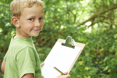 Boy Prendre des notes sur Trip Nature School Champ Banque d'images