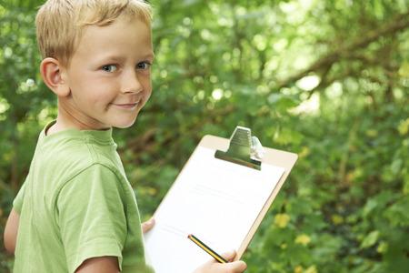 Boy tomando notas en la escuela de la naturaleza Campo de viaje