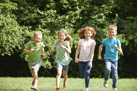 7 year old girl: Group Of Happy Children Running Towards Camera Through Field
