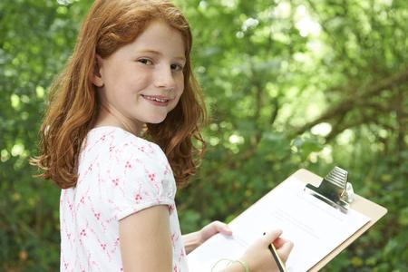 portapapeles: Chica tomando notas en la escuela de la naturaleza Campo de viaje Foto de archivo