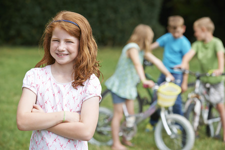 7 year old girl: Group Of Children Outdoors Playing On Bikes Stock Photo