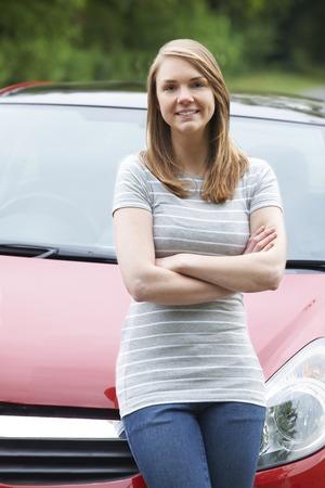 female driver: Proud Young Female Driver Standing In Front Of Car Stock Photo