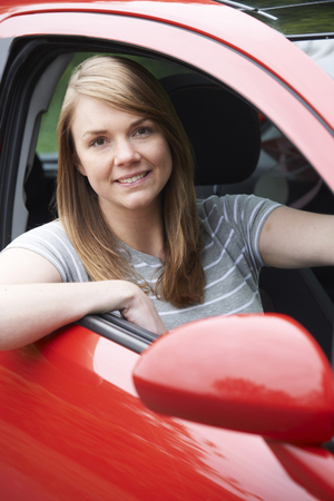 female driver: Portrait Of Young Female Driver In Car Stock Photo