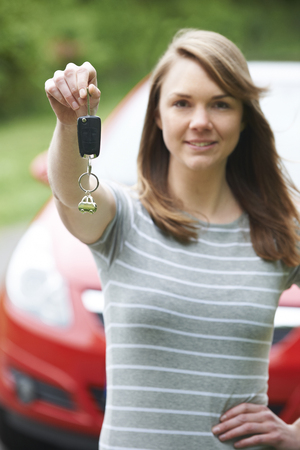 female driver: Young Female Driver Holding Car Keys In Front Of Vehicle