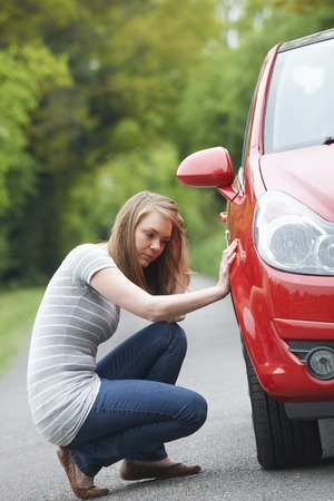 puncture: Female Motorist With Puncture On Country Road Stock Photo