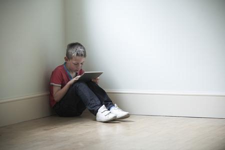 niños tristes: Niño infeliz que se sienta en la habitación con la tableta digital
