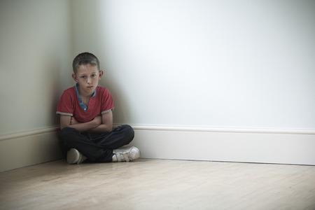 niños sentados: Niño infeliz que se sienta en la esquina de la habitación