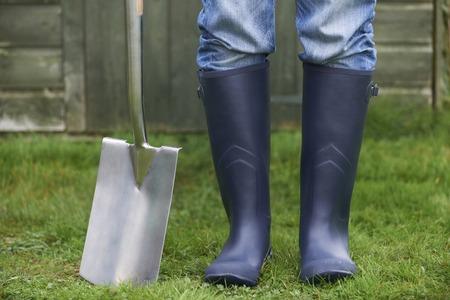wellingtons: Close Up Of Man Wearing Wellingtons Holding Garden Spade