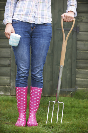 wellingtons: Woman In Pink Wellingtons Holding Garden Fork And Cup Stock Photo