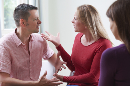 counsellor: Couple Arguing In Front Of Relationship Counsellor Stock Photo