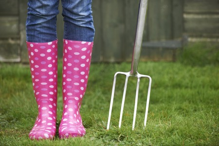 galoshes: Close Up Of Woman Wearing Pink Wellingtons Holding Garden Fork