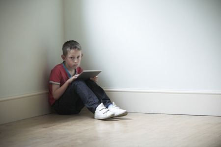 child boy: Unhappy Child Sitting In Room With Digital Tablet