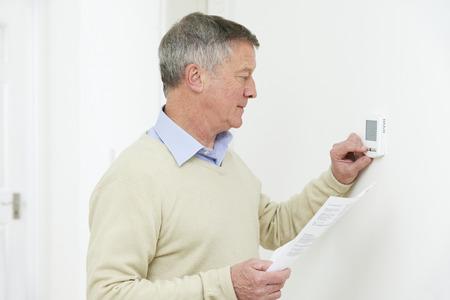 ahorro energia: Hombre mayor preocupante con Bill bajando la calefacción del termostato