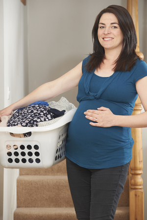 doing chores: Pregnant Woman Doing Chores At Home Stock Photo