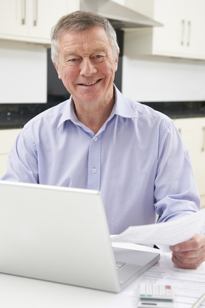 home finances: Smiling Senior Man Checking Home Finances Stock Photo