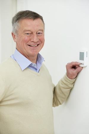 adjusting: Smiling Senior Man Adjusting Central Heating Thermostat