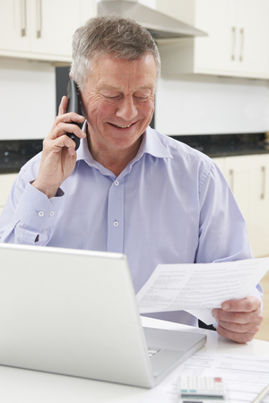 silver surfer: Senior Man On Phone Checking Personal Finances Stock Photo