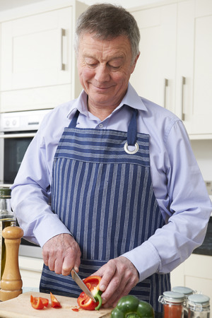 home cooking: Senior Man Preparing Meal In Kitchen