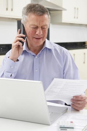 factura: Infeliz hombre mayor en el teléfono Consulta de Bill Foto de archivo