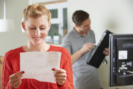 cable tv: Happy Woman Looking At Bill For TV Installation